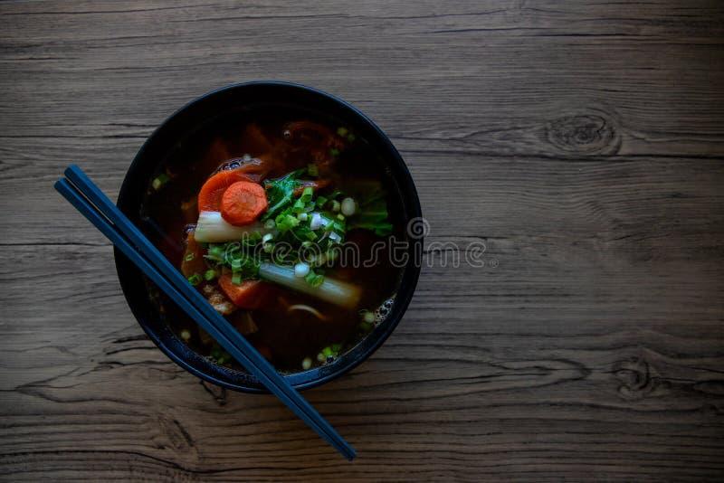 在陶瓷碗的菜汤在木桌上 中国汤服务用棍子 东部汤碗顶视图照片 免版税库存照片