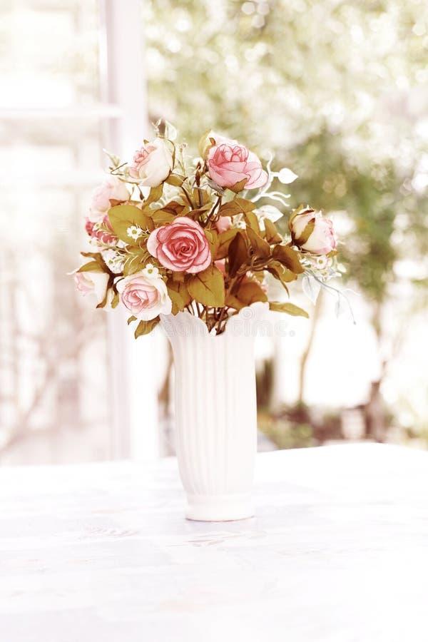 在陶瓷花瓶的桃红色人为玫瑰在窗口附近 库存照片