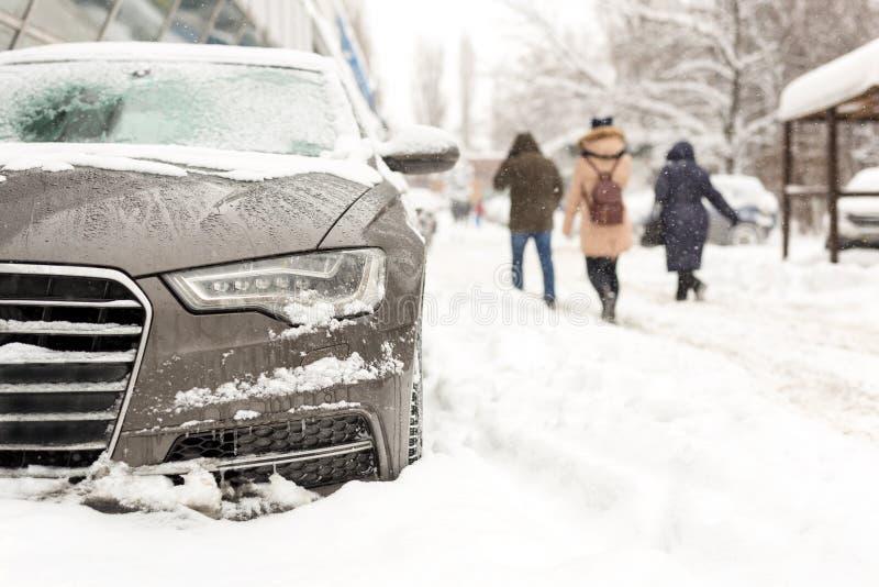 在随风飘飞的雪停放的汽车在城市街道 重的冬天降雪 走的人们,当猛烈的雪和风时 风暴飞雪 图库摄影