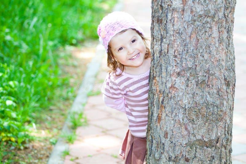 在隐藏少许结构树的女孩之后 免版税图库摄影