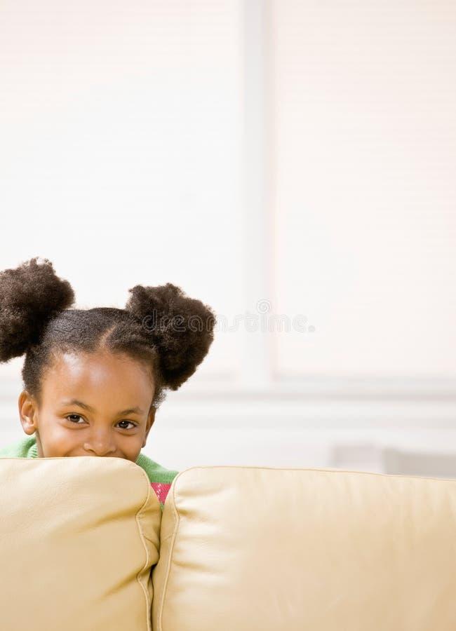 在隐藏恶作剧沙发的女孩之后的非洲人 库存图片