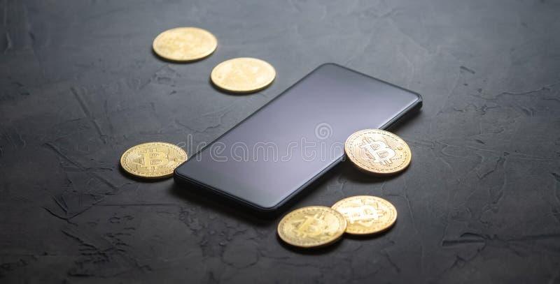 在隐藏货币的收入:金币bitcoin和智能手机在灰色背景 水平的框架 免版税库存照片