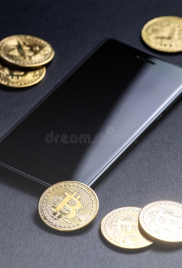 在隐藏货币的收入:金币bitcoin和智能手机在黑暗的背景 垂直的射击 免版税库存照片