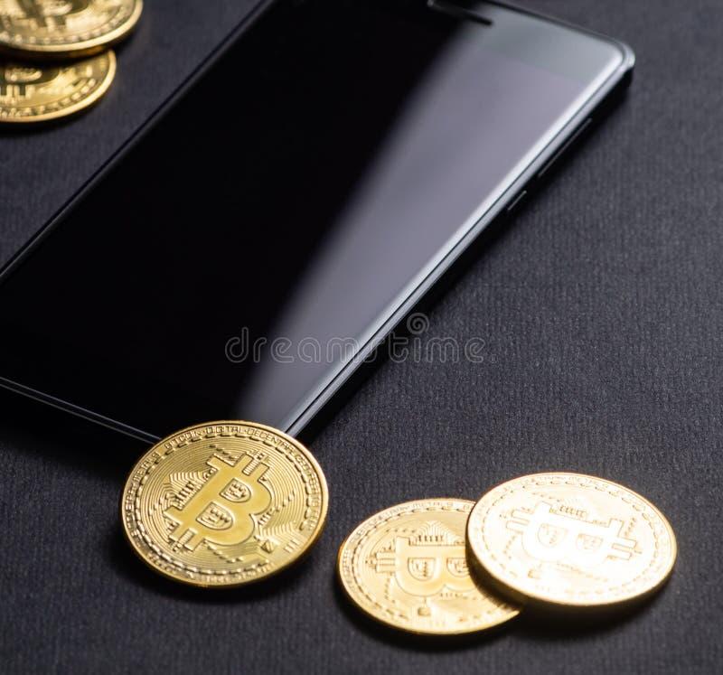 在隐藏货币的收入:金币bitcoin和智能手机在黑暗的背景 方形框架 免版税库存照片