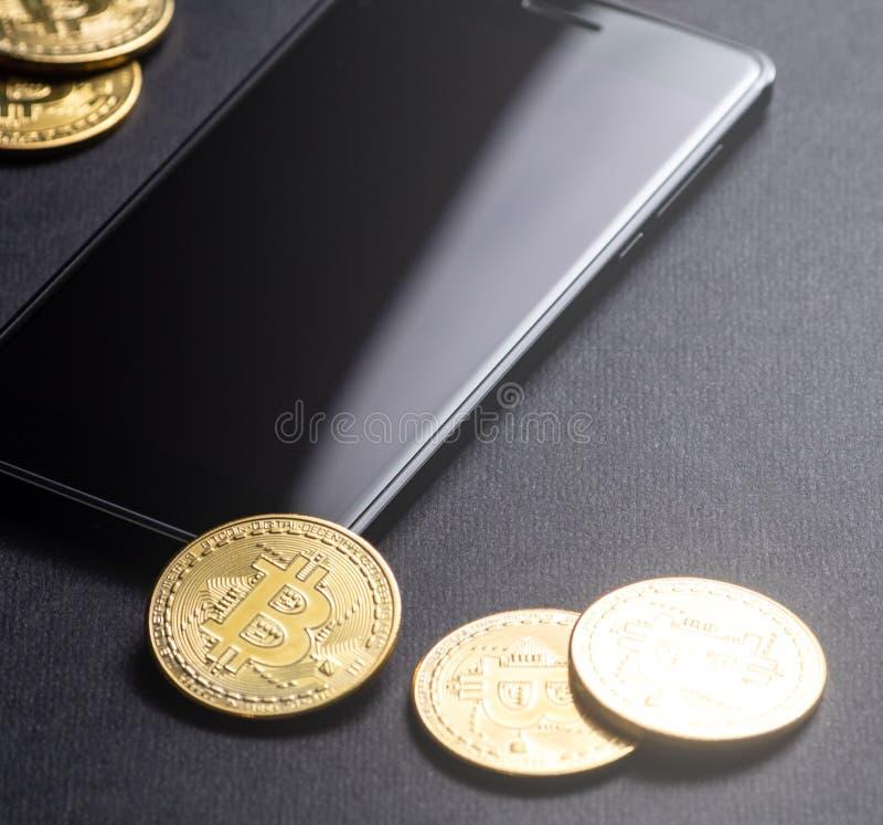 在隐藏货币的收入:金币bitcoin和智能手机在黑暗的背景 方形框架 图库摄影