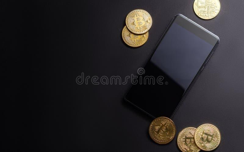在隐藏货币的收入:金币bitcoin和智能手机在黑暗的背景 水平的框架 免版税库存照片