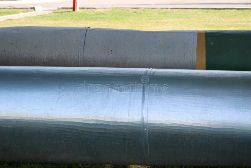 在隔离的两个大管子从在炼油厂的锡,石油化学制品,化工厂背景 免版税库存照片