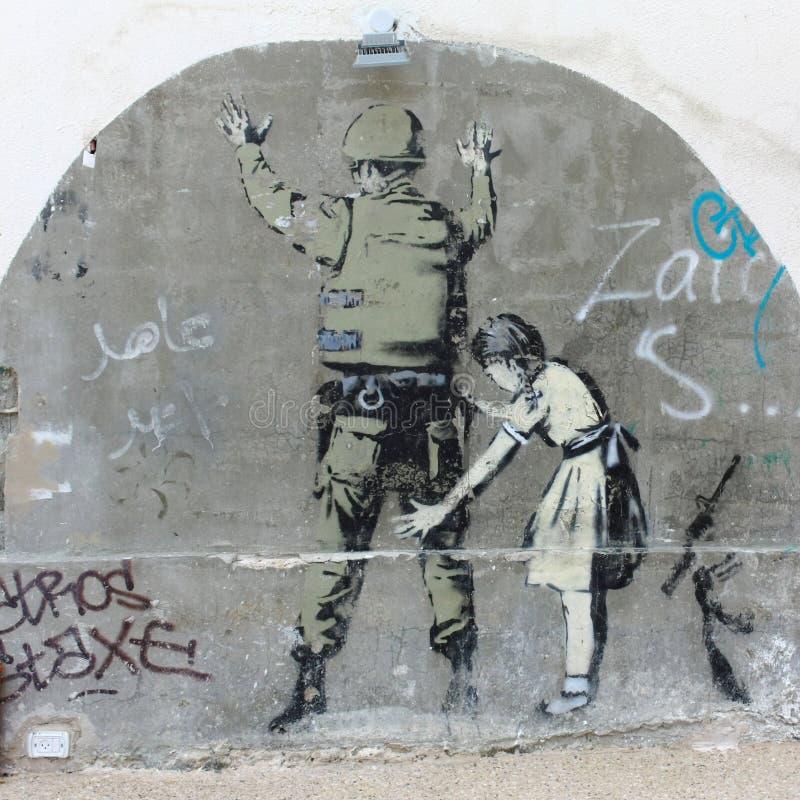 在隔离墙,伯利恒,以色列附近的Banksy街道画 库存照片