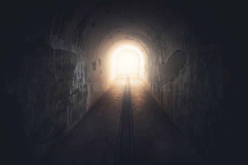 在隧道的末端的光 在被放弃的地堡的长的地下具体走廊,被定调子 库存照片
