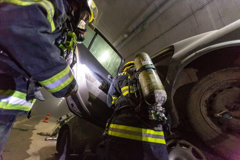 在隧道里面的车祸场面,抢救从汽车的消防队员人 免版税库存图片