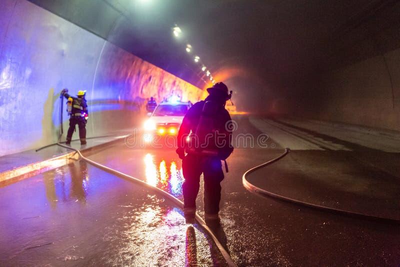 在隧道里面的车祸场面,抢救从汽车的消防队员人 图库摄影