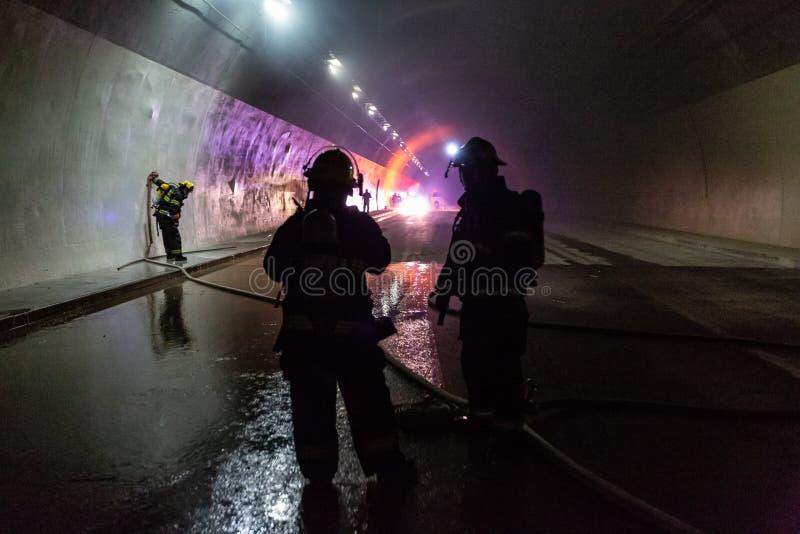 在隧道里面的车祸场面,抢救从汽车的消防队员人 免版税库存照片