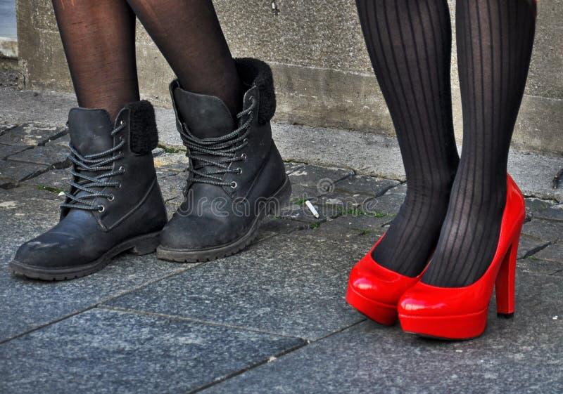 在黑和红色鞋子的妇女腿 库存照片