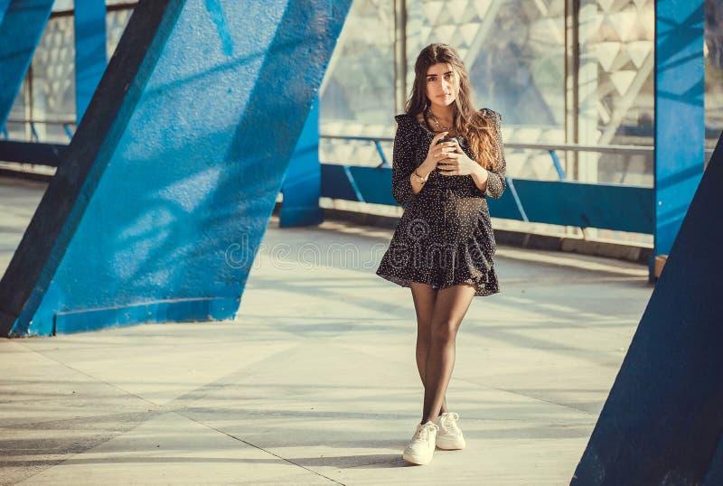 在难看的东西区域之间的专栏的深色的女孩身分 在都市晴朗的空间的年轻女人饮用的咖啡 库存照片