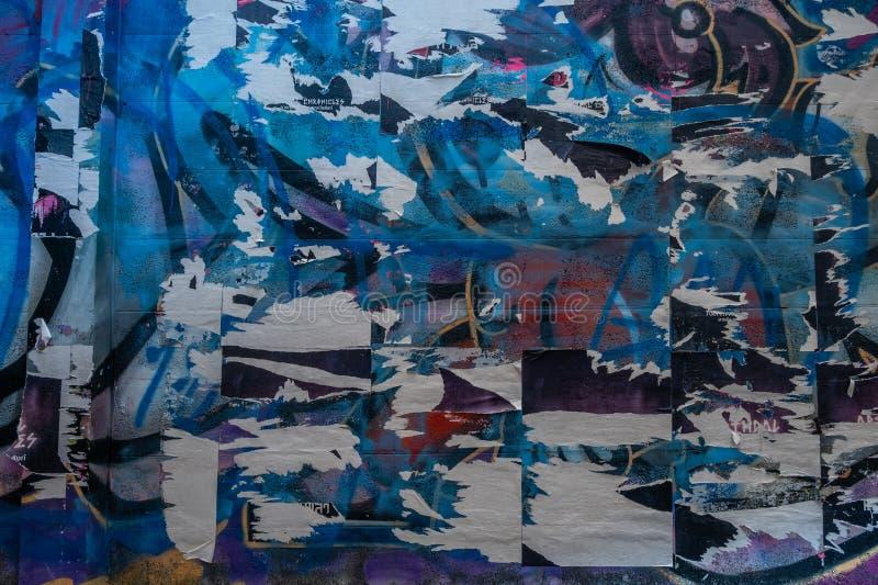 在难看的东西老墙壁上的五颜六色的被撕毁的海报作为创造性和抽象背景 免版税库存图片