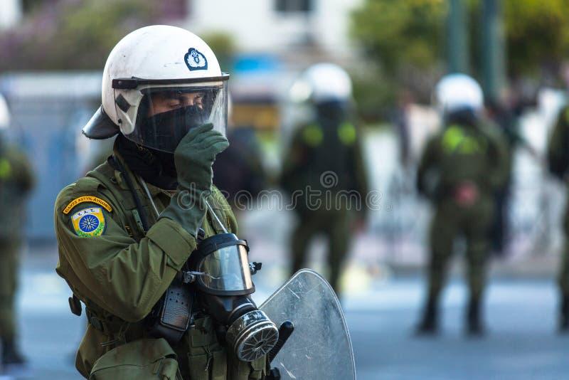 在雅典大学前面的一次集会期间与他们的盾的防暴警察,躲藏起来 免版税库存图片