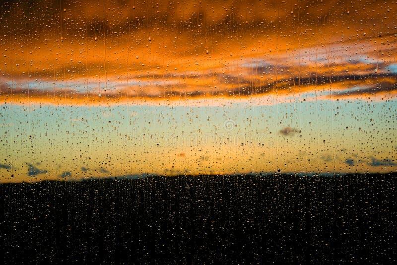 在雨下的日落通过窗口 免版税图库摄影