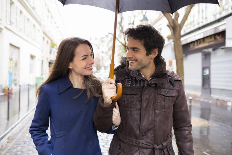 在雨下的英俊的夫妇在街道上 库存图片