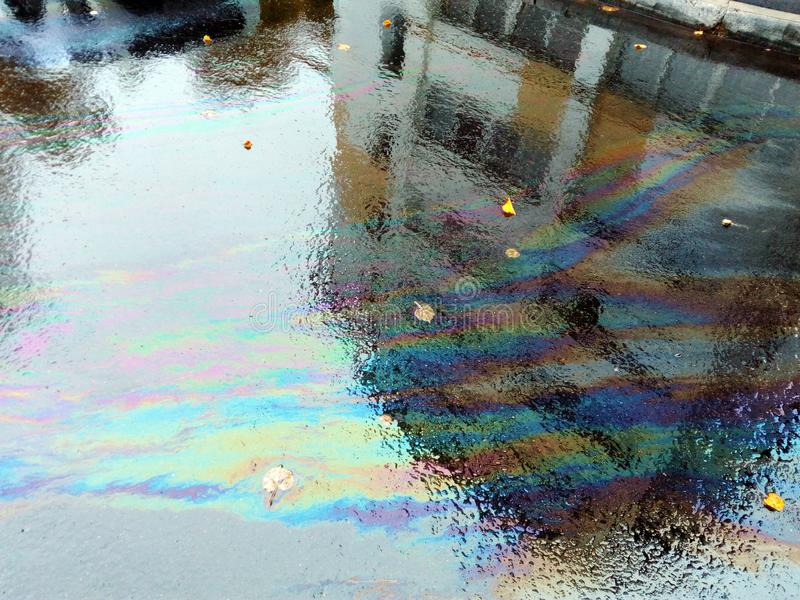 在雨五颜六色的水坑的沥青 免版税库存图片