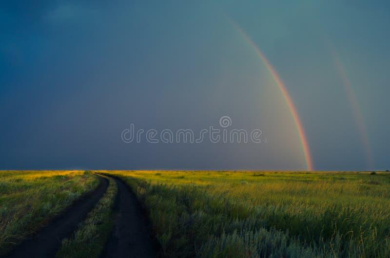 在雨以后的双重彩虹在暴风云背景  在域的路 免版税库存照片