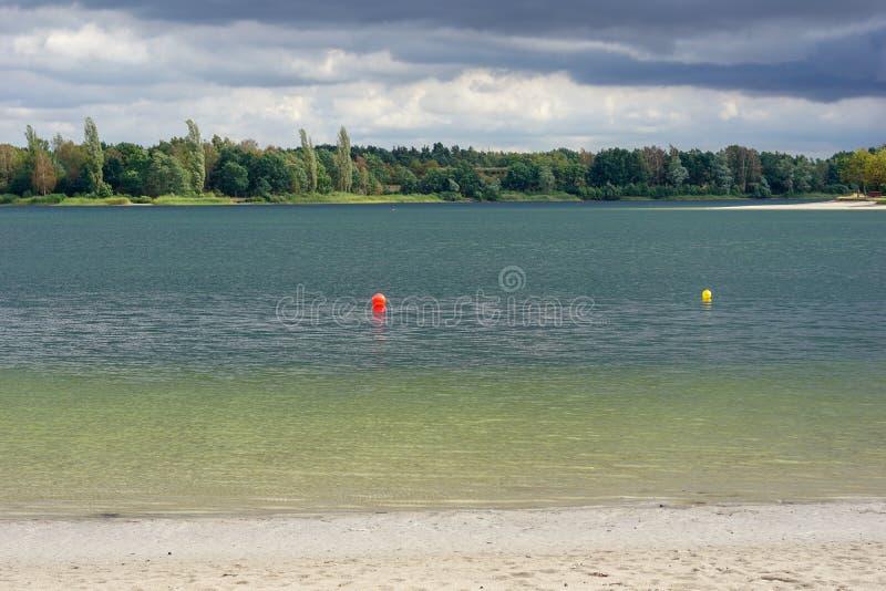 在雨以后的天蓝色的湖 免版税库存照片