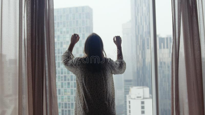 在雨期间,有肮脏的头发的哀伤的荒凉的女孩在curban建筑学的窗口看 免版税库存图片