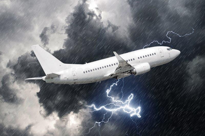 在雨期间,白色乘客飞机离开,恶劣天气雷暴雷击  免版税图库摄影