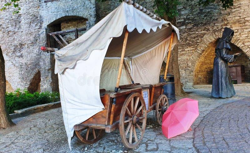 在雨镇中心桃红色伞以后的塔林奥尔德敦在老在木轮子的石头块中世纪老帐篷站立街道Mo 免版税库存图片