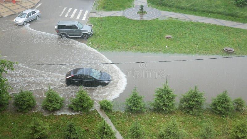 在雨,一条坏路,在大雨以后的水期间汽车通过水坑乘坐 免版税库存图片