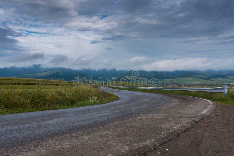 在雨,在天空的stormclouds以后的空,弯曲的柏油路 免版税库存照片