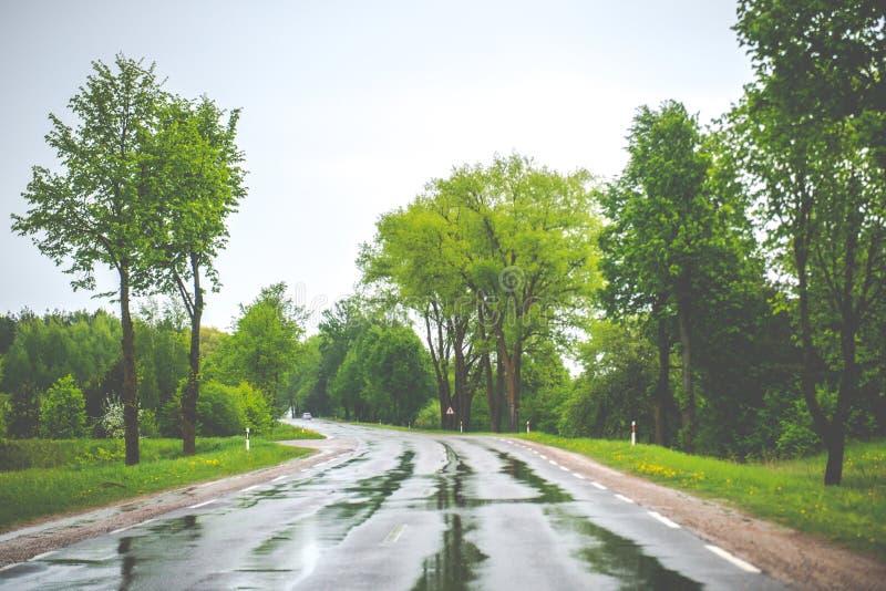 在雨,湿的全部以后柏油路和有一点危险去 免版税库存照片