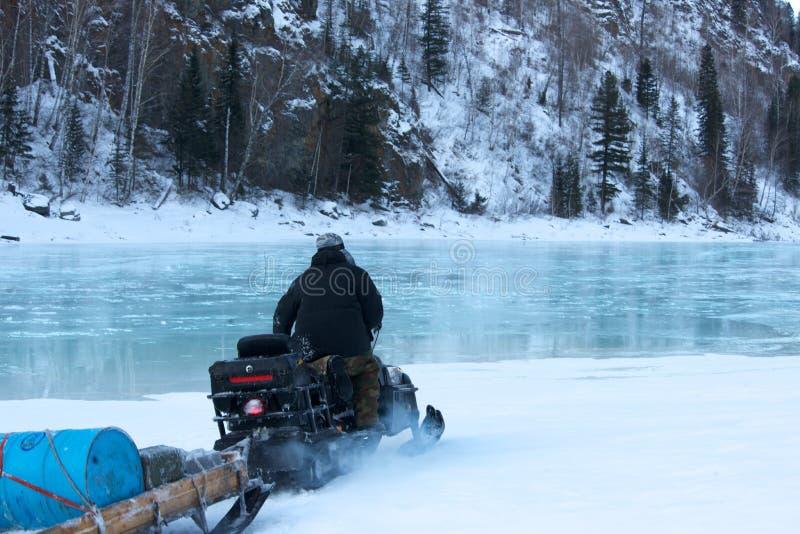 在雪上电车结冰的水的人骑马 免版税图库摄影