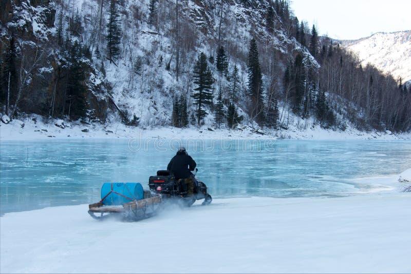 在雪上电车结冰的水的人骑马 库存照片