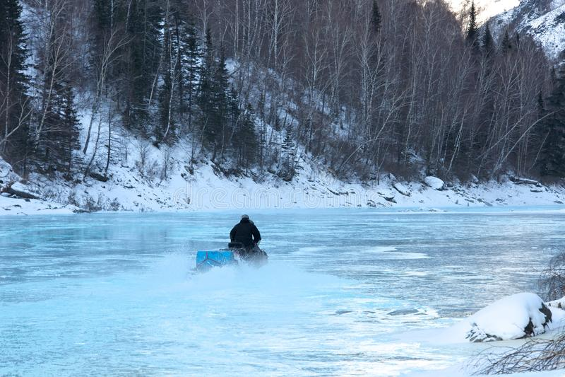 在雪上电车结冰的水的人骑马 免版税库存图片