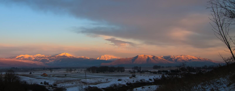 在雪下的山与被日光照射了晚上太阳 免版税库存图片