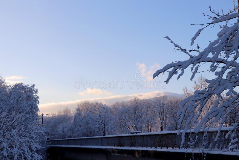 在雪下的桥梁在云彩的一个看法 免版税库存照片