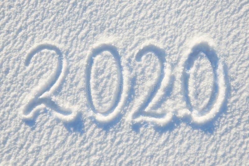 2020在雪写的文本为纹理或背景-寒假概念好日子,与阴影的明亮的光,平的位置,上面 库存图片