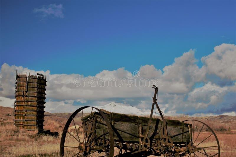 在雪前面的古色古香的农场设备和水塔加盖了山 免版税库存照片