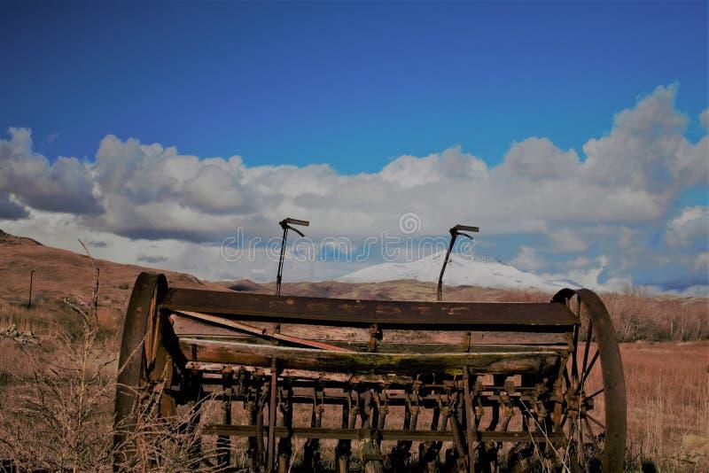 在雪加盖的山前面的古色古香的农场设备 免版税图库摄影