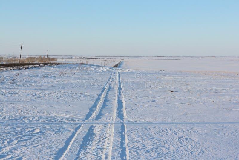 从在雪原中的一辆雪上电车追踪 库存图片
