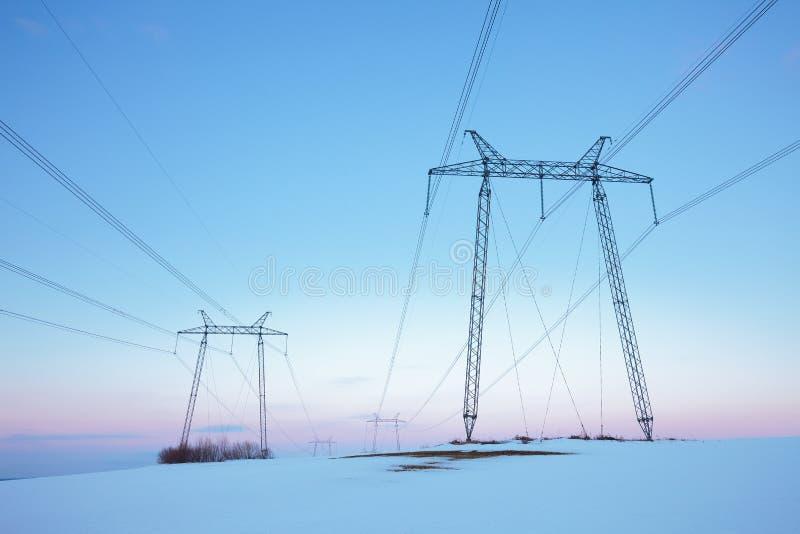 在雪原的输电线在淡色日落 免版税库存图片