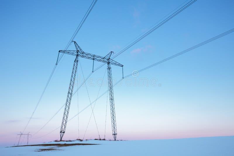 在雪原的输电线在淡色日落 图库摄影