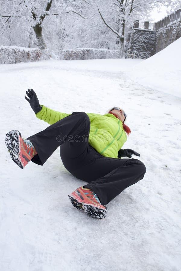在雪和冰滑倒的妇女 免版税图库摄影