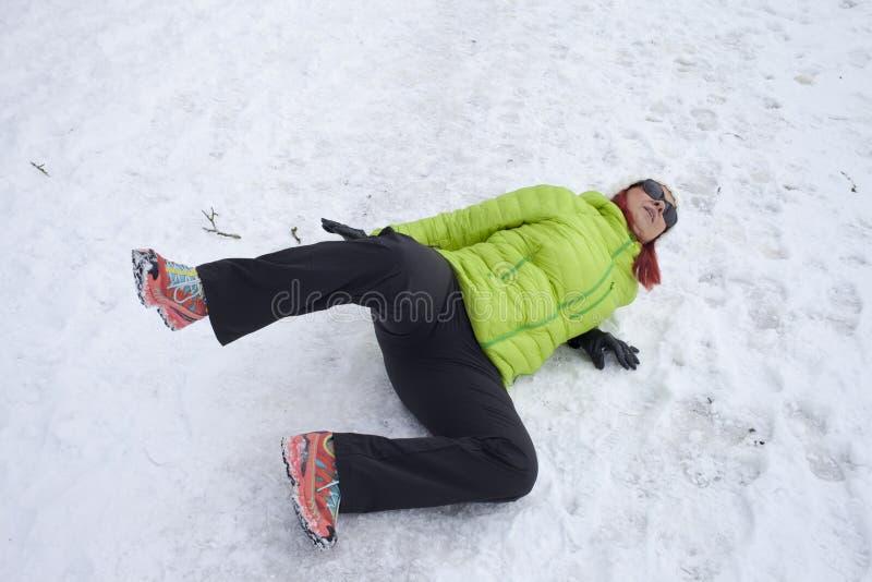 在雪和冰滑倒的妇女 库存图片