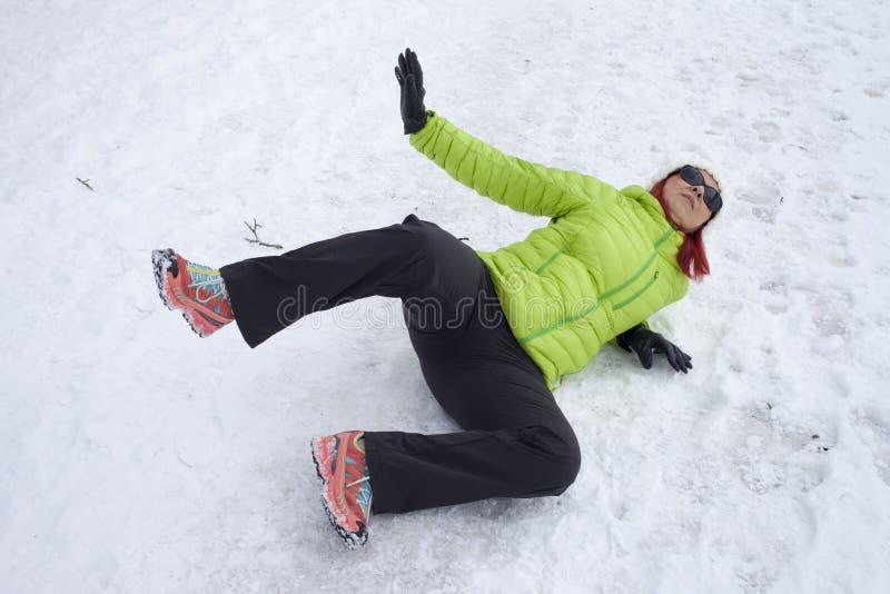 在雪和冰滑倒的妇女 库存照片