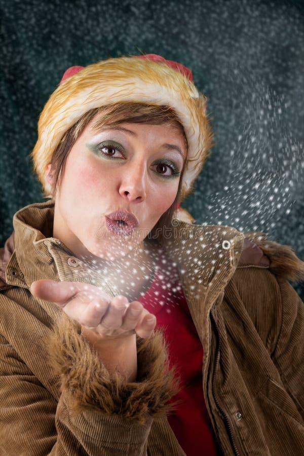 在雪和星形外面的圣诞节神仙吹的亲吻 免版税库存照片