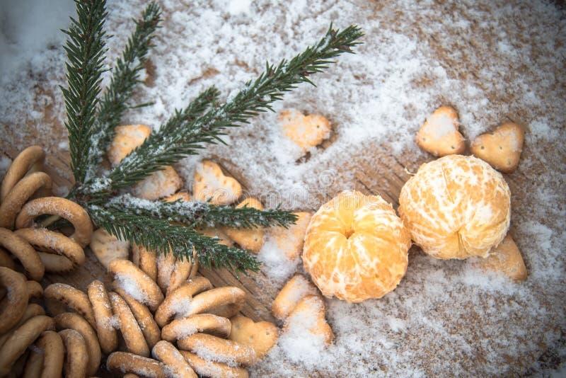 在雪在一张木桌上,新年,静物画的蜜桔 图库摄影