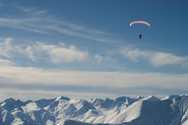 在雪山的滑翔伞 免版税库存照片