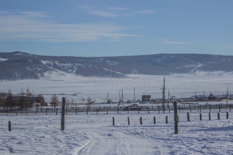 在雪报道的路风景对村庄用山脉和蓝天背景 免版税图库摄影
