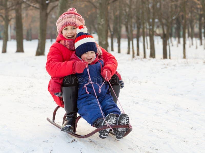 在雪撬的两个愉快的孩子 库存照片